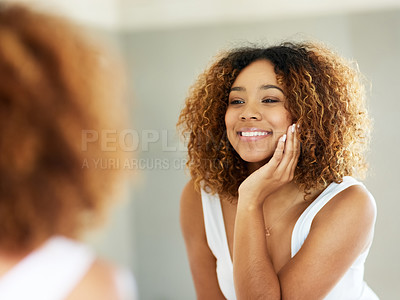 Buy stock photo Shot of an attractive young woman admiring herself in the bathroom mirror