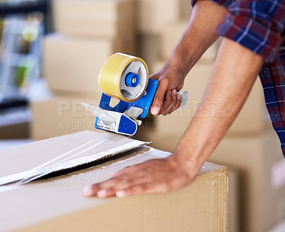 Buy stock photo Shot of an unidentifiable man using a tape dispenser to close a box while moving house