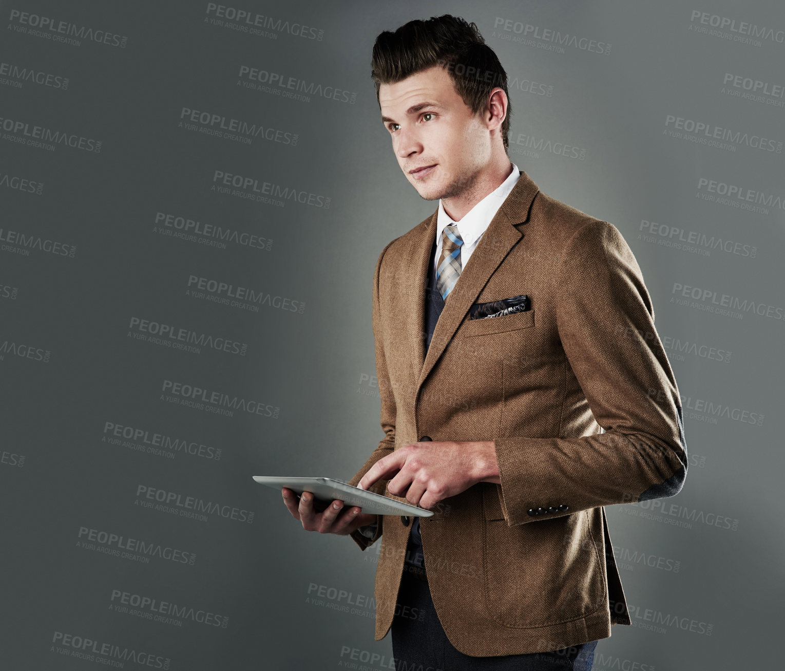 Buy stock photo Studio shot of a young businessman using his tablet against a grey background