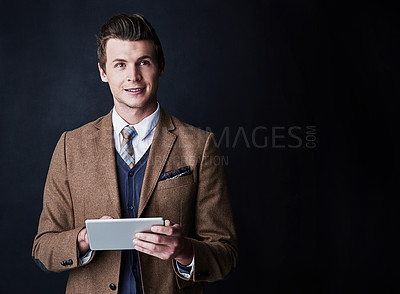 Buy stock photo Studio shot of a young businessman using his tablet against a dark background