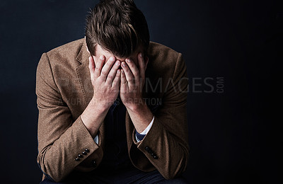 Buy stock photo Studio shot of a businessman looking worried against a dark background