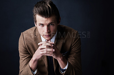 Buy stock photo Studio shot of a young businessman against a dark background