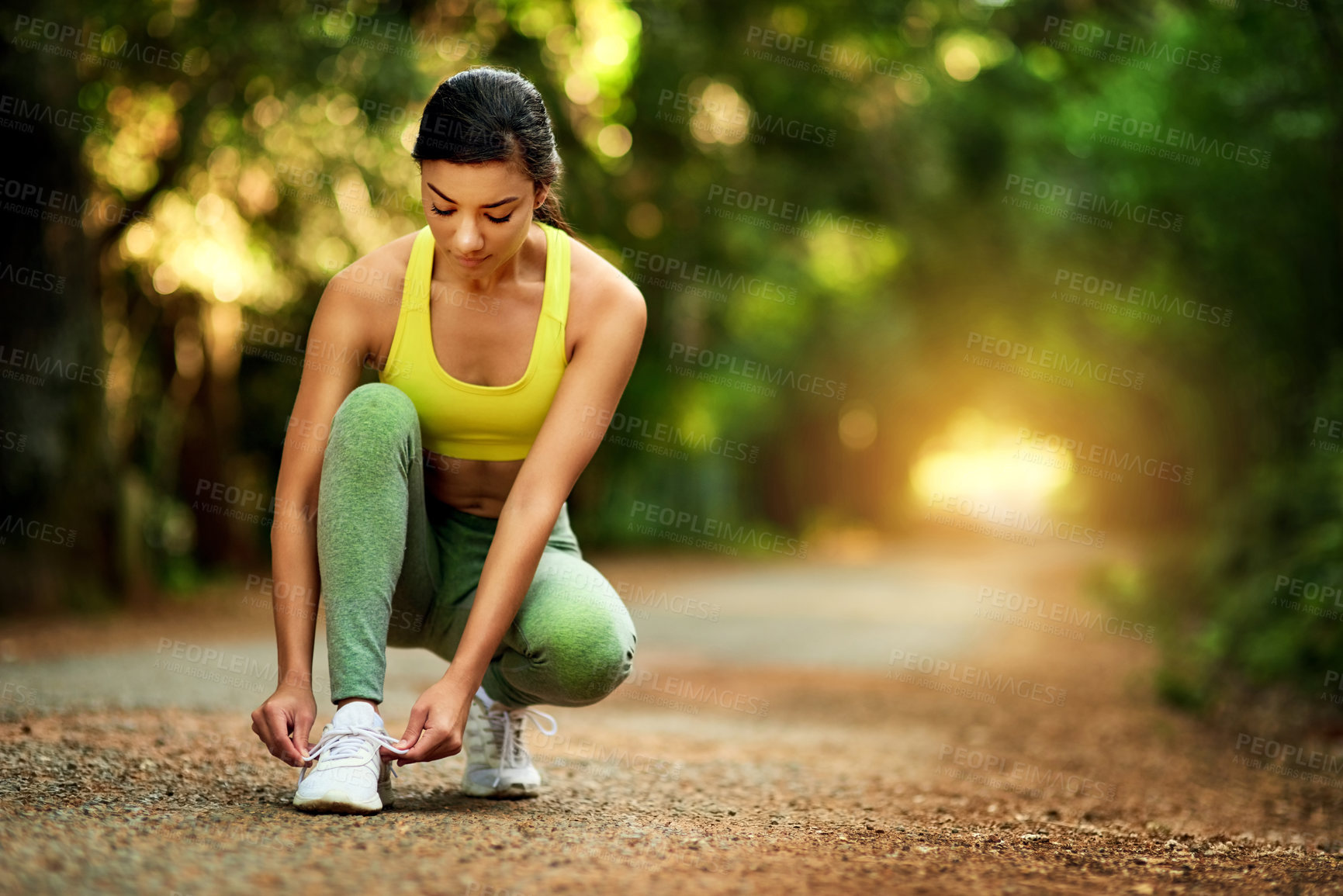 Buy stock photo Shot of a sporty young woman tying her shoelaces before a run