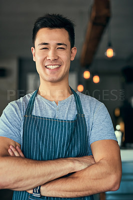 Buy stock photo Cropped portrait of a young man standing with his arms folded in his coffee shop