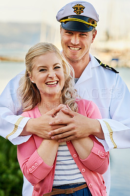 Buy stock photo Portrait of a man in a navy uniform hugging his wife while they stand on the docks