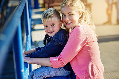 Buy stock photo Portrait of a mother posing with her little boy on her lap while enjoying a day outside