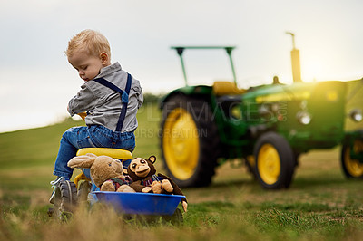 Buy stock photo Shot of an adorable little boy carting stuffed animals in a toy truck around a farm