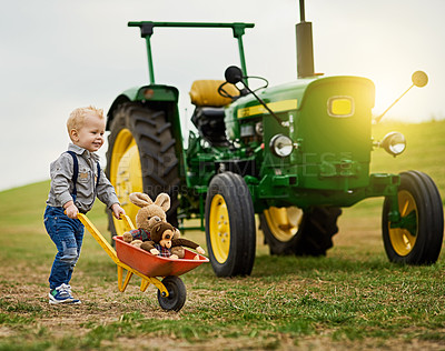 Buy stock photo Shot of an adorable little boy pushing a toy wheelbarrow filled with stuffed animals on a farm