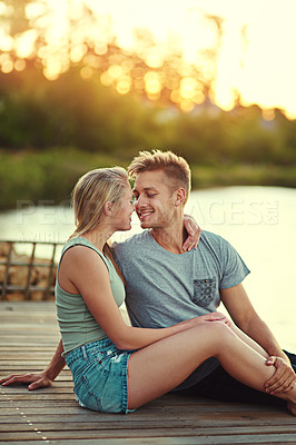 Buy stock photo Cropped shot of an affectionate young couple sitting together at a lake outside
