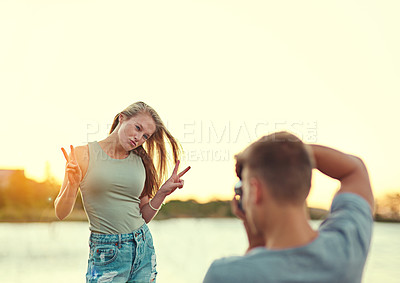 Buy stock photo Cropped shot of a young man taking a photo of his girlfriend outside