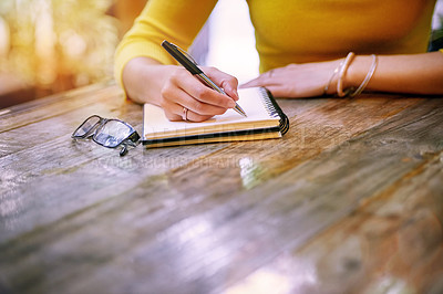 Buy stock photo Cropped shot of a woman sitting at a table and writing in her notepad