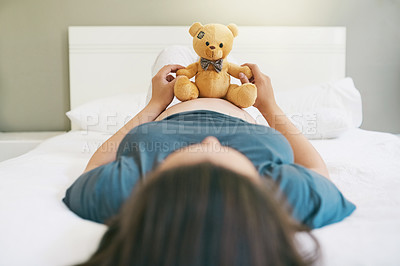 Buy stock photo Shot of a pregnant woman playing with her unborn baby's teddy bear