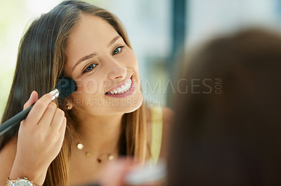 Buy stock photo Shot of an attractive young woman applying makeup to her face with a brush