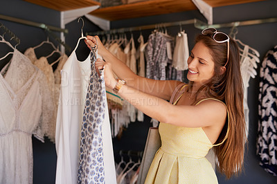 Buy stock photo Cropped shot of a young woman browsing through the clothes in a boutique