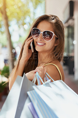 Buy stock photo Shot of a young woman talking on her phone while out shopping
