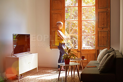 Buy stock photo Shot of a mature woman standing by a window at home deep in thought
