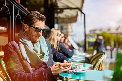 Buy stock photo Shot of a young man sitting at a sidewalk cafe in Paris reading a text on a cellphone