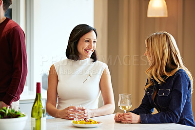 Buy stock photo Shot of a two young women talking together in a kitchen with their partners in the background