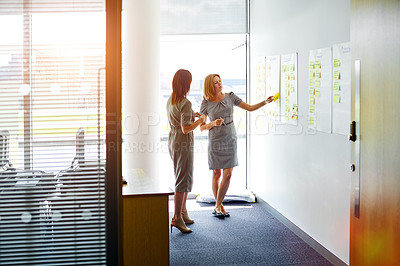 Buy stock photo Shot of two female colleagues talking together in a modern office