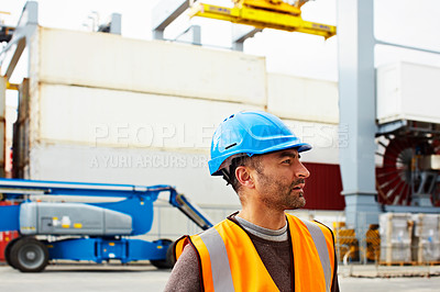 Buy stock photo Shot of a young man in workwear standing outside on a large commercial dock