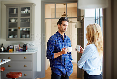 Buy stock photo Shot of a young couple drinking coffee together in their kitchen