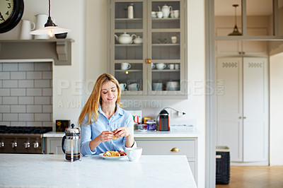 Buy stock photo Shot of a young woman drinking coffee and eating breakfast in her kitchen