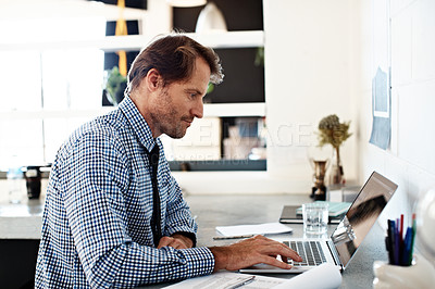Buy stock photo Shot of a businessman working on a laptop at his desk in an office