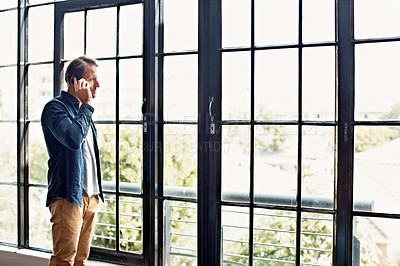 Buy stock photo Shot of a mature man talking on a cellphone while standing by windows in his apartment