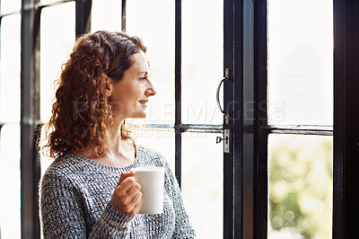 Buy stock photo Shot of a mature woman standing in her home drinking a coffee and looking through a window