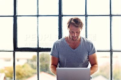 Buy stock photo Shot of a mature man sitting on a window sill at home using a laptop