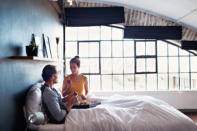 Buy stock photo Shot of a smiling mature couple enjoying breakfast in bed together in the morning