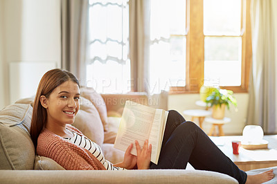 Buy stock photo Portrait of a smiling young woman sitting on her sofa reading a book