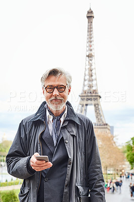 Buy stock photo Shot of a handsome mature man using a cellphone in Paris with the Eiffel Tower in the background