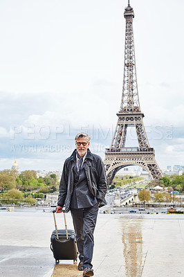 Buy stock photo Portrait of a handsome mature man walking with his suitcase in front of the Eiffel Tower