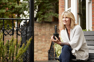 Buy stock photo Shot of a mature woman sitting on a bench on her front porch drinking a coffee