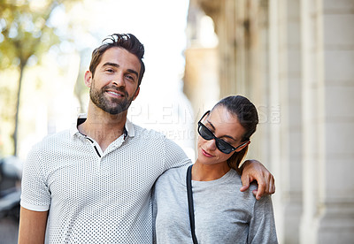 Buy stock photo Portrait of an affectionate young couple walking together in the city