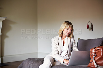 Buy stock photo Shot of a mature businesswoman sitting on a hotel bed using a laptop