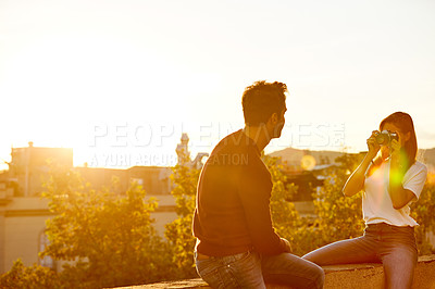 Buy stock photo Shot of a young woman taking a photo of her boyfriend while sitting on a balcony overlooking the city