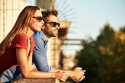 Buy stock photo Shot of a smiling young couple leaning on a balcony in the city looking at the view