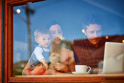 Buy stock photo Shot of smiling couple and their little girl standing in the window of their bakery