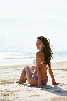 Buy stock photo Shot of a young woman sitting on the beach enjoying her vacation