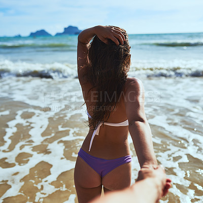 Buy stock photo Shot of a young woman leading someone's into the water