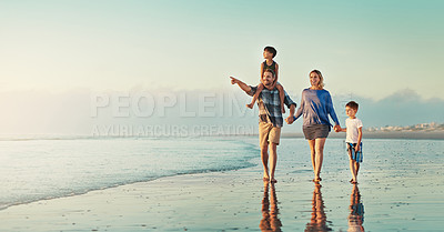 Buy stock photo Shot of a happy family of four enjoying a walk along the beach