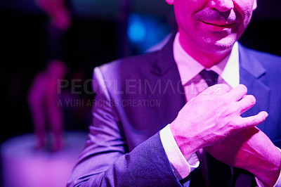 Buy stock photo Shot of a seedy businessman adjusting his tie in a go go bar with a woman dancing on a pole behind him