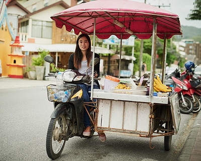Buy stock photo Portrait of a young food vendor waiting by her stall in Thailand