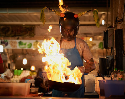 Buy stock photo Shot of an unidentifiable food vendor wearing a helmet while flambeing something in a pan
