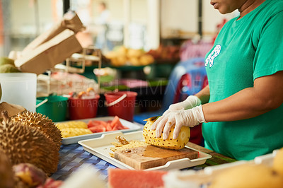 Buy stock photo Shot of an unidentifiable woman slicing fruit in a Thai food market