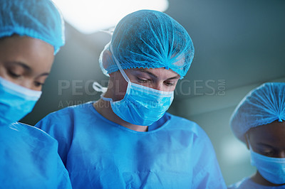 Buy stock photo Shot of a team of surgeons performing a medical procedure in an operating room