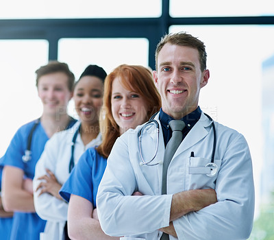 Buy stock photo Portrait of a team of confident young doctors standing in a line