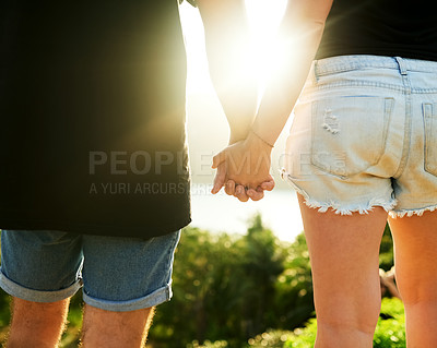 Buy stock photo Rearview shot of an unrecognizable young couple standing hand in hand outside
